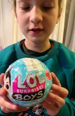 Girl holds a L.O.L. Surprise Boy ball