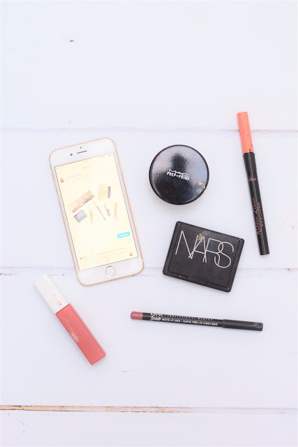A collection of beauty products and an iPhone showing an Instagram post