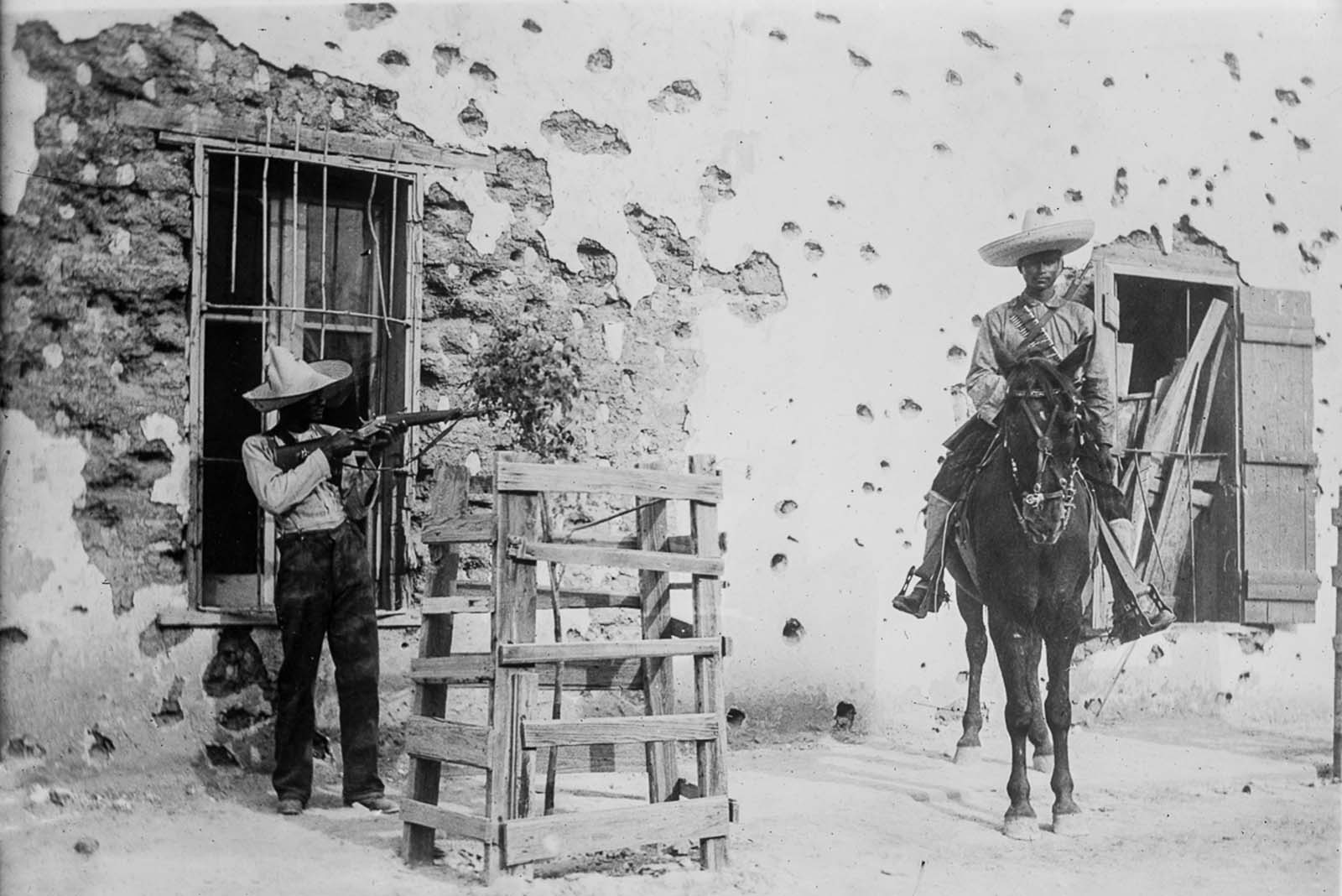 Rebels in front of an adobe house riddled with bullet holes in Ciudad Juárez.