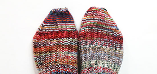 Tops of feet wearing colorfully striped hand knit wool socks on a white background, showcasing a prominent dark red stripe in the same place on each sock despite differencs throughout the rest of the colors.
