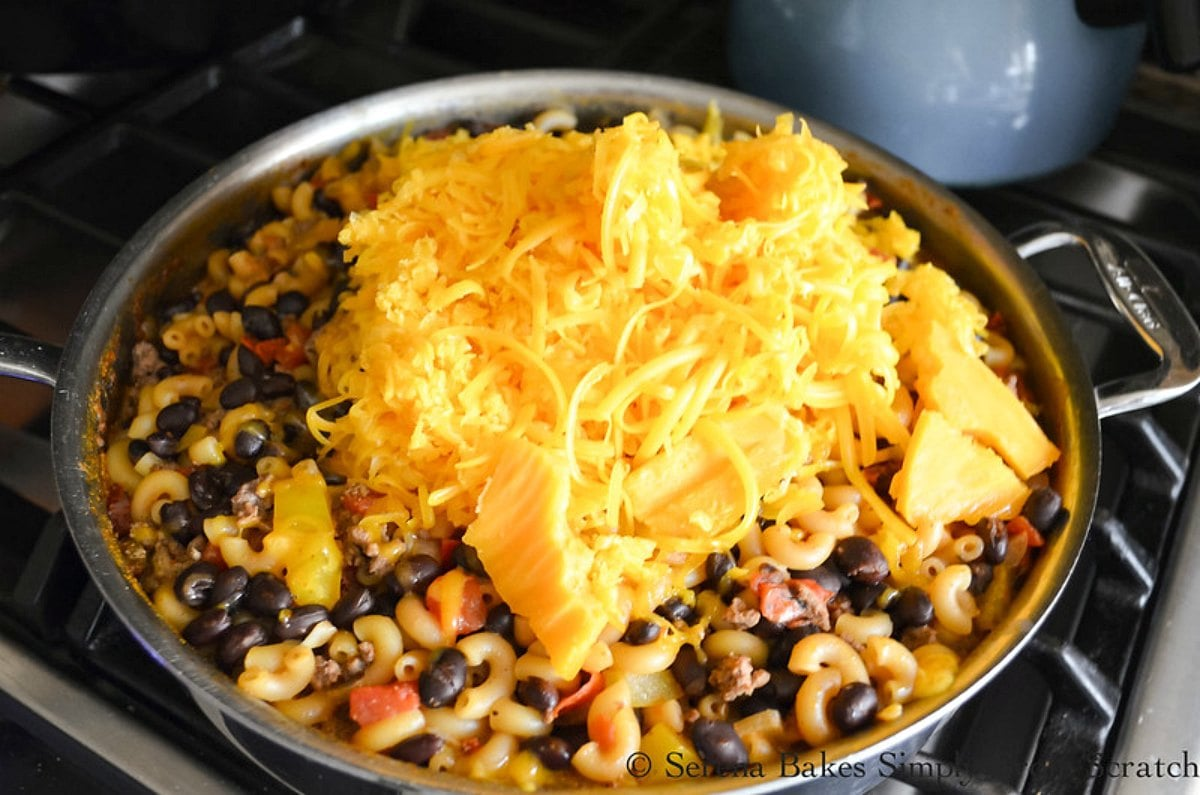 Cheese added to Chili Mac in a large pan.