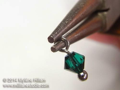 Simple loop formed on a head pin strung with an emerald Swarovski bicone, using round nose pliers.