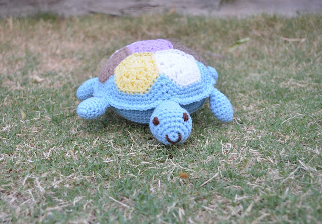 A blue crocheted turtle is creeping towards us on the lawn. Its happy blue face has dark brown embroidered eyes and smile.  Its 'shell' is patterned with a crocheted hexagon patchwork in pastel colours.