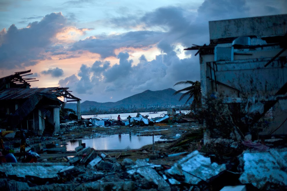 Typhoon Haiyan survivors walk through the ruins of their neighborhood on the outskirts of Tacloban, central Philippines on Nov. 13. (David Guttenfelder/Associated Press) #