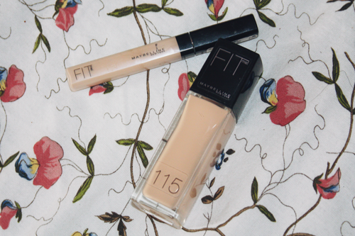 maybelline fit me foundation and concealer side by side on a bed