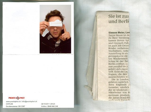 Photoscan of a photobooth photo with a person holding part of a newspaper article which talks about the work of Taryn Simon.