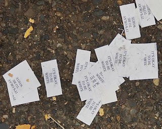 "Photo showing slips of paper on the ground, with printed text, ""It's okay to be white"""