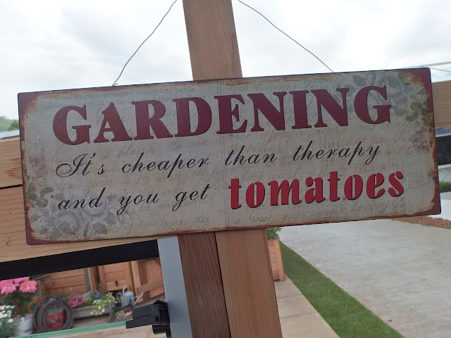 Garden sign saying it's better than therapy and you get tomatoes