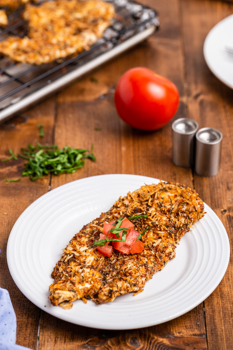 Photo of a Keto Parmesan Chicken Cutlet topped with chopped tomato and basil on a white plate.