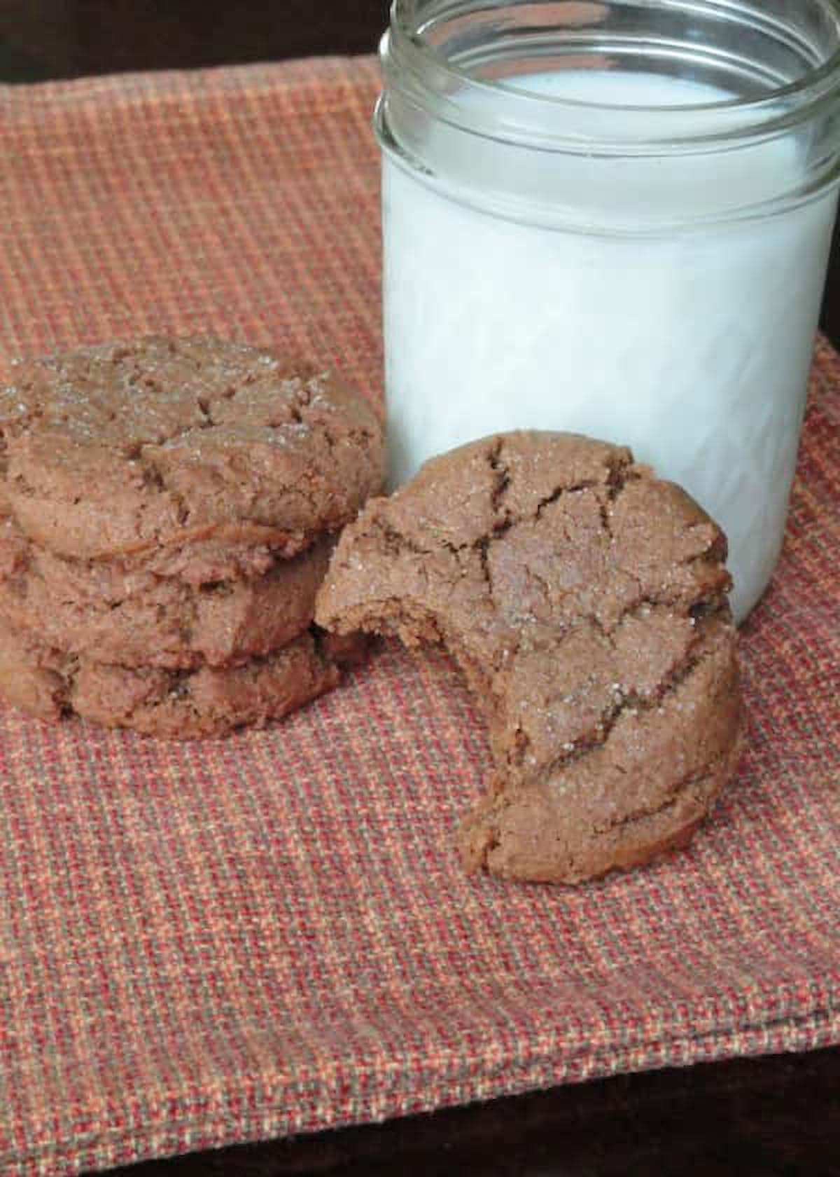 Molasses Cookies stacked on an orange kitchen towel with one Molasses Cookie resting on its side with a bite missing.