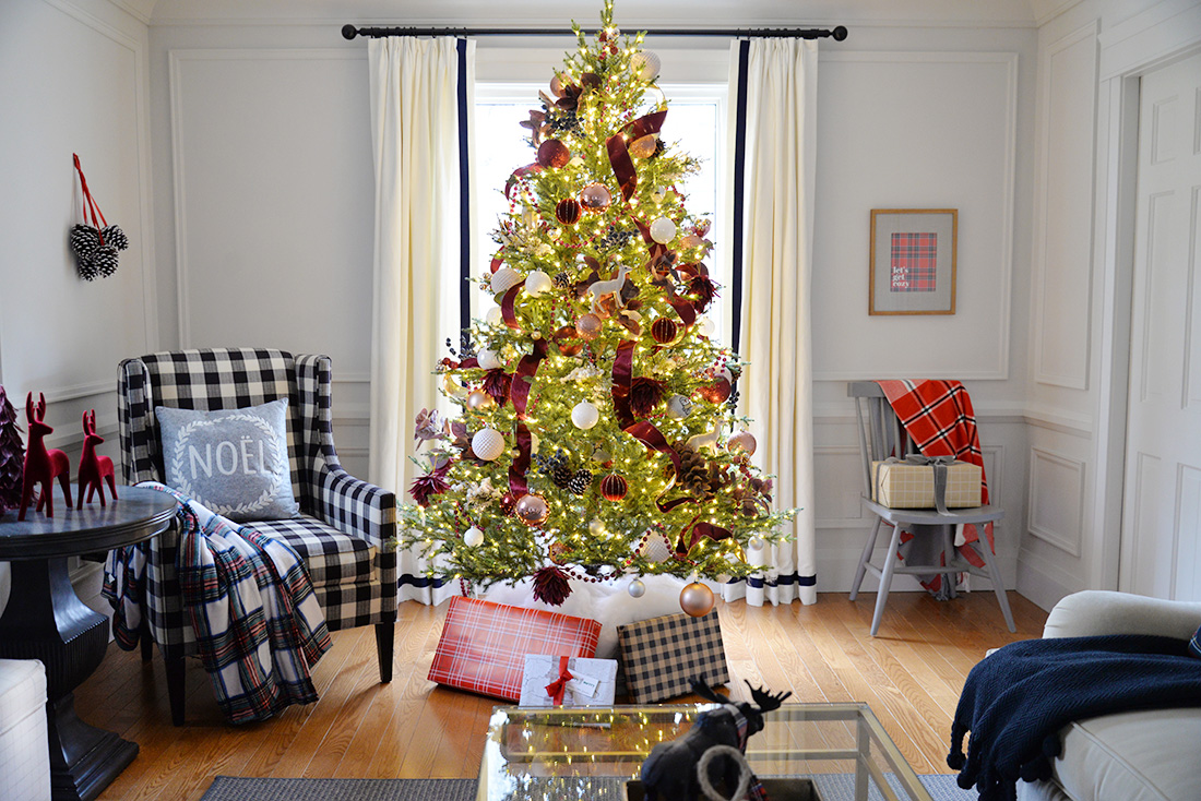 Living room decorated for Christmas with red and white Christmas tree. Canadian Tire mulberry collection Christmas ornaments. Buffalo plaid chair.