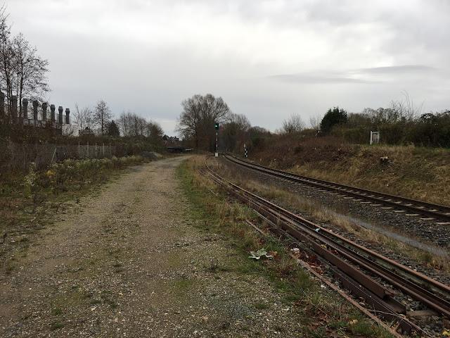 Ein Schotterweg führt neben den beiden Gleisen bis zu einem Bahnsignal, das gerade Grün zeigt. Das Abstellgleis ist fast zugewachsen mit Gras und es liegen alte Schienen darin. Neben dem Gleis rechts ist ein kleiner Hand. Dahinter Schrebergärten.