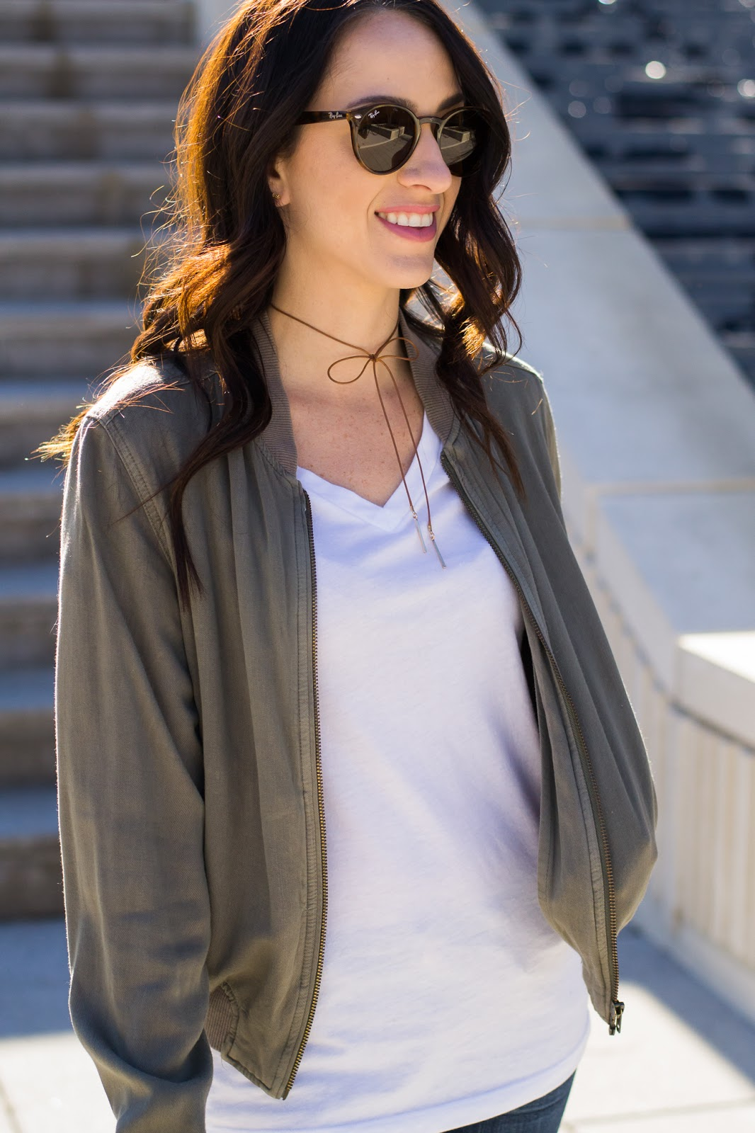 Dressing up a white tee with a bomber jacket and bow choker necklace