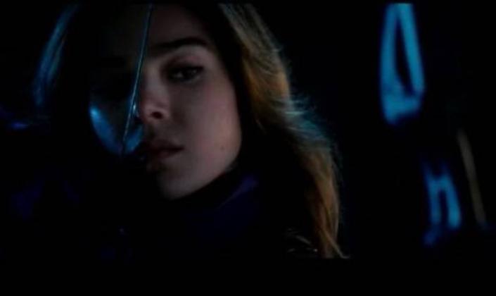 Imagem de capa: a personagem Kate Bishop, interpretada por Kailee Steinfeld, uma garota branca com longos cabelos castanhos em um traje arroxeado com um arco e flecha na mão, mirando em alguma coisa ao longe, na noite.