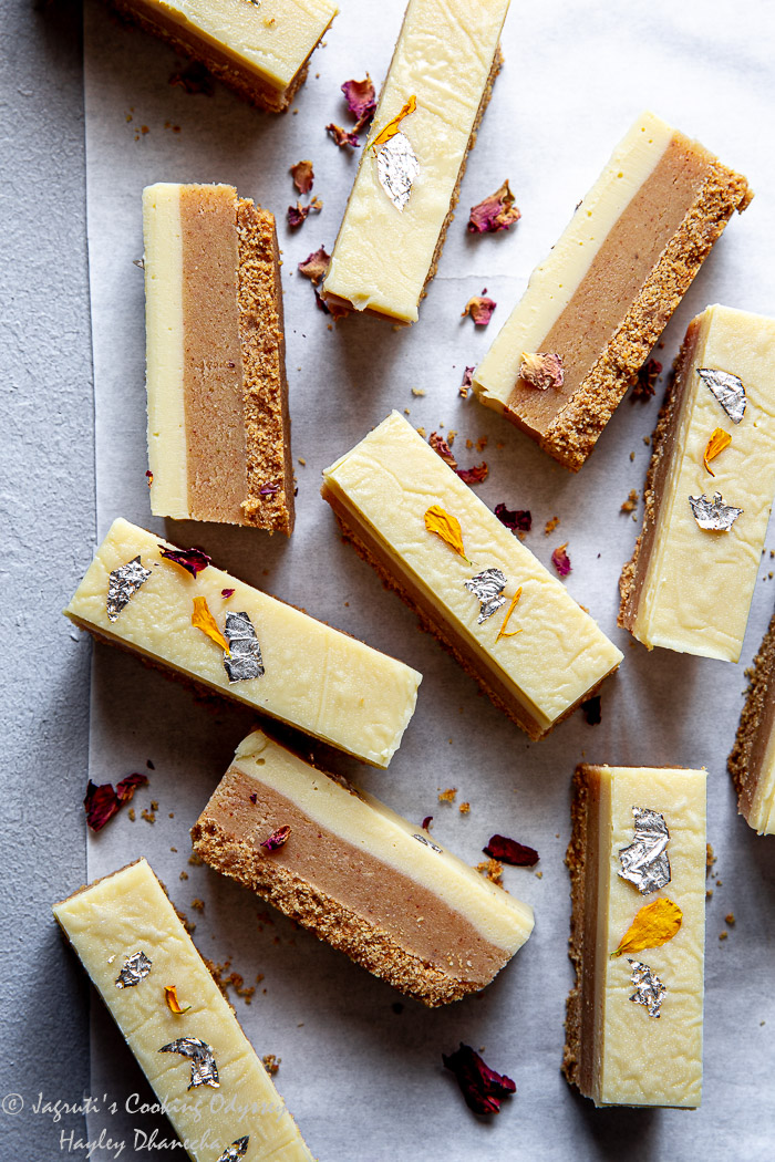 Slices of Almond butter barfi bars or milk powder barfi on parchment paper garnished with edible rose petals