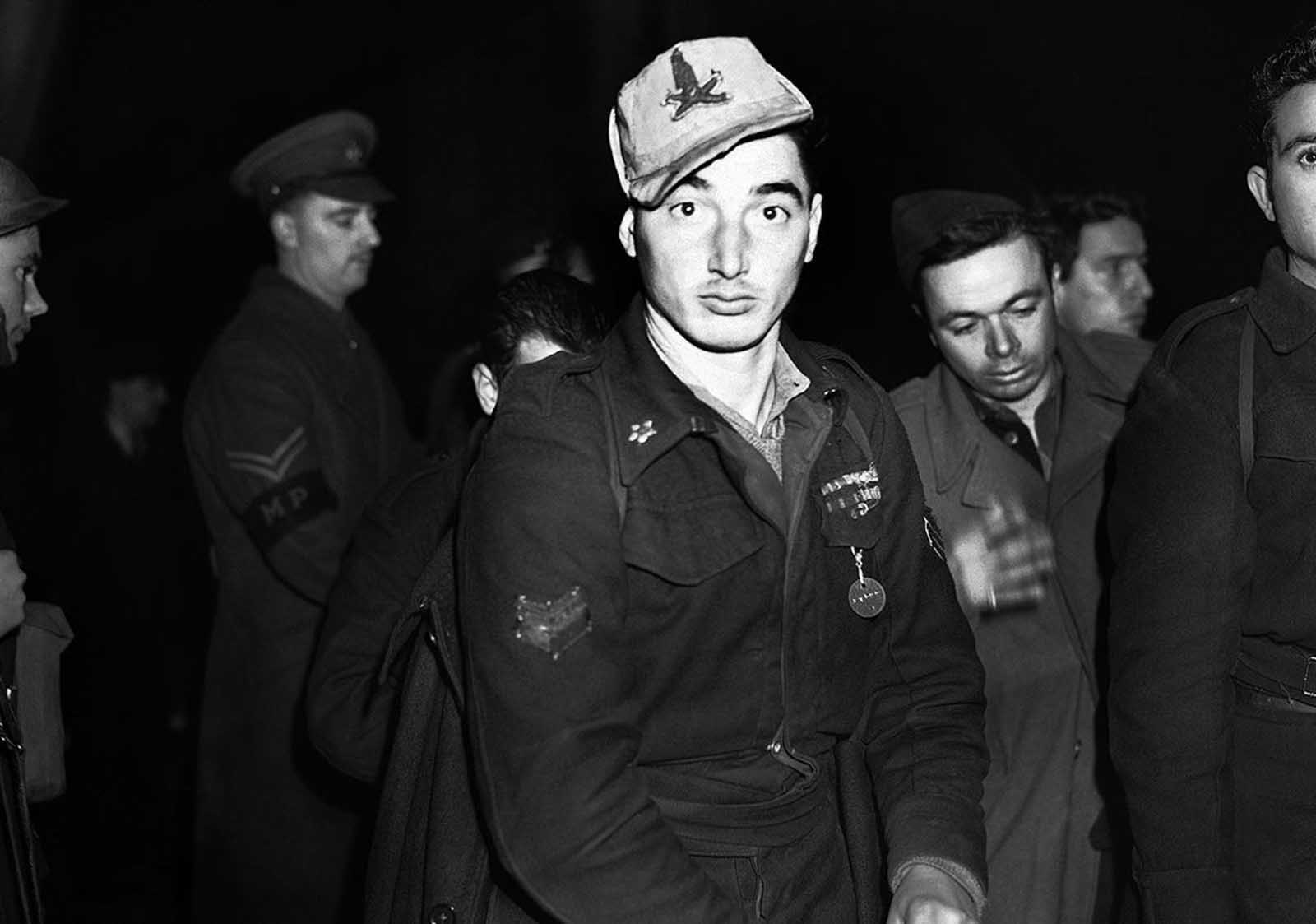 One of the many Italian prisoners of war captured in Libya, who arrived in London on January 2, 1942. This one is still wearing his Africa Corps cap.