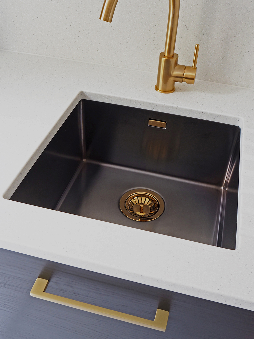 French For Pineapple Blog - contemporary gold brass tap with anthracite undermounted sink with gold waste and pale flecked mistral mist worktop and splashback