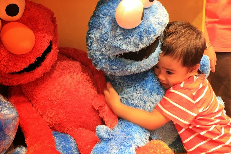 a boy hugging a big cookie monster stuff toy