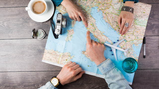 hands pointing to Rome on a map. with coffee, compass, and a toy airplane