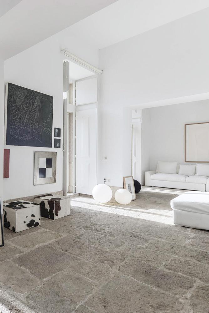 Salón blanco simple y minimalista con un suelo de piedra espectacular y objetos de arte