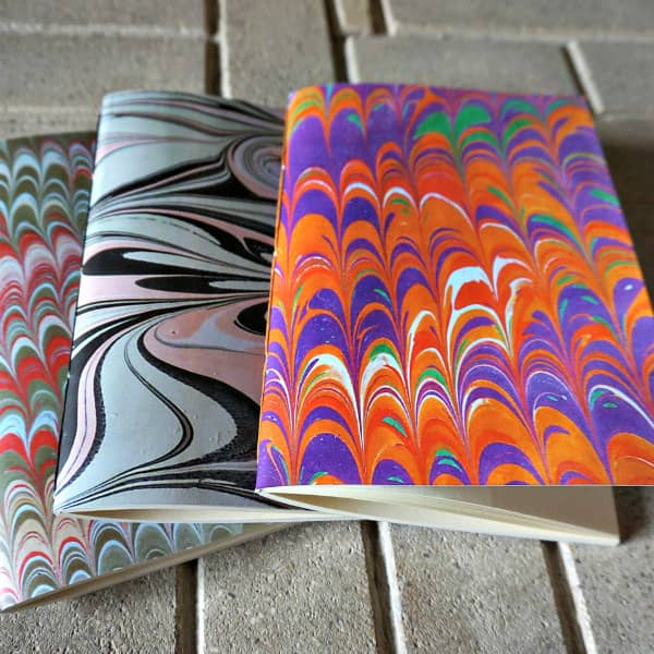 three small sketchbooks with colorful marbled covers