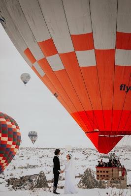 Pareja de novios en un paisaje nevado y los invitados dentro de un globo