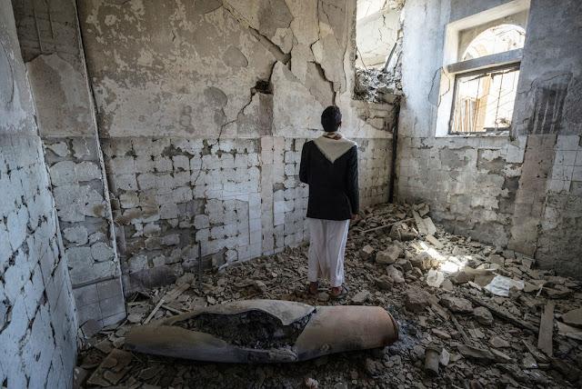 Un hombre se encuentra junto a la carcasa de un misil en un antiguo edificio del gobierno en la ciudad de Saada, Yemen.OCHA/Giles Clarke