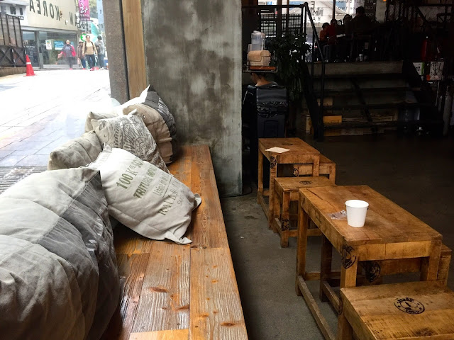 Cushioned window seat and low wooden tables in Allegiance Cafe in Nampo, Busan, South Korea