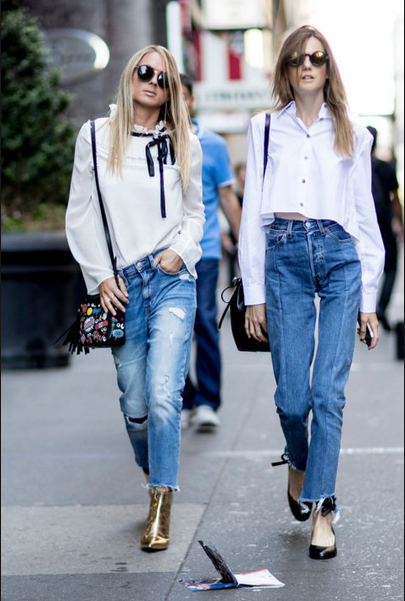 two girls wearing jeans pants and white tops