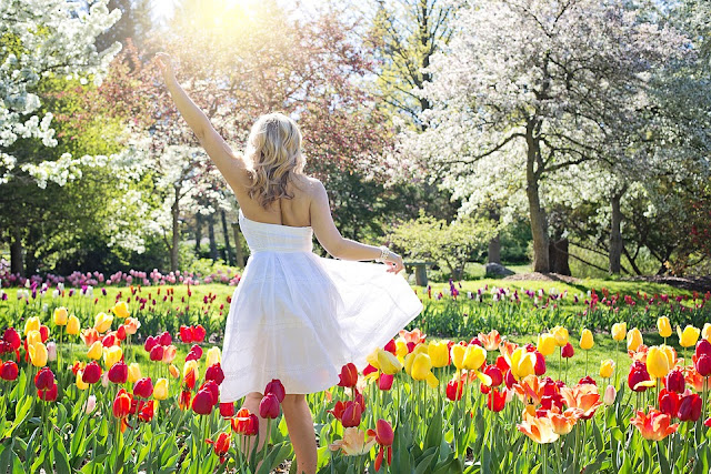 Mulher saúda a Natureza em meio a um campo repleto de flores na Primavera