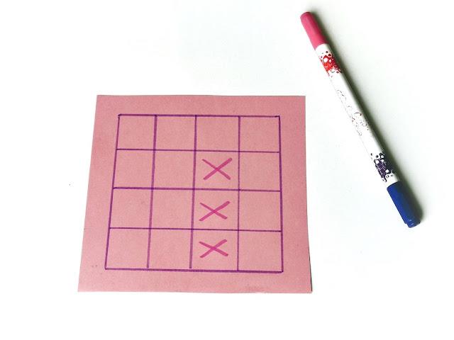 na zdjęciu narysowana na różowym papierze plansza 4x4 pola a na niej zaznaczone trzy pierwsze pola, przylegające do siebie, obok lezy pisak