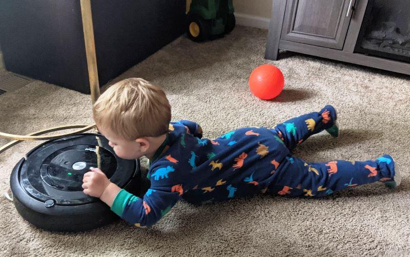 Montessori toddlers. Maximum Effort. Child with vacuum
