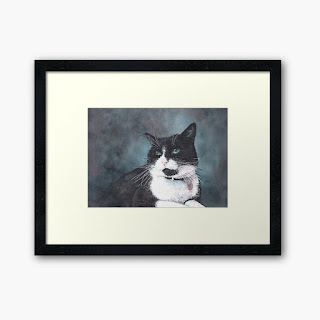 A framed print of a watercolor painting of a black and white cat