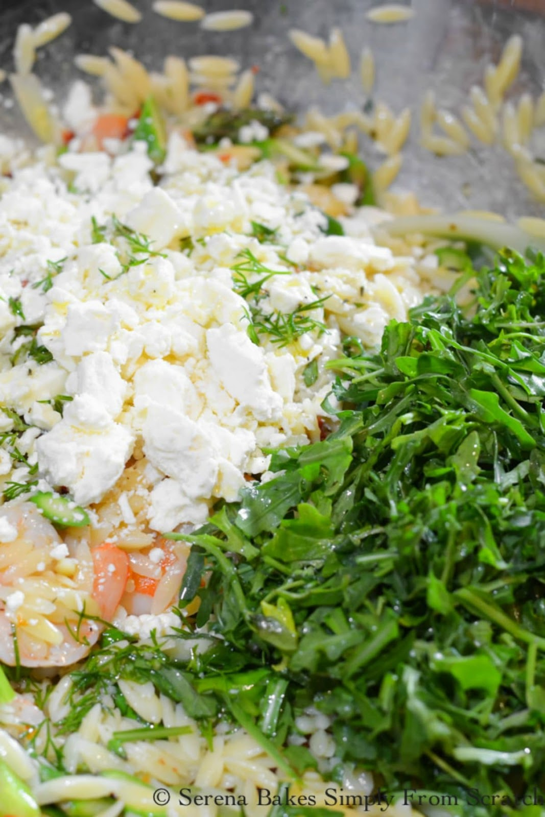 Chopped Arugula, Feta Cheese and Chopped Dill on top of Shrimp Orzo Pasta Salad.