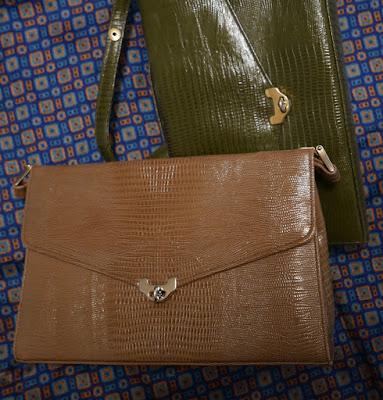 A tan handbag sitting on top of an identically-shaped olive green handbag