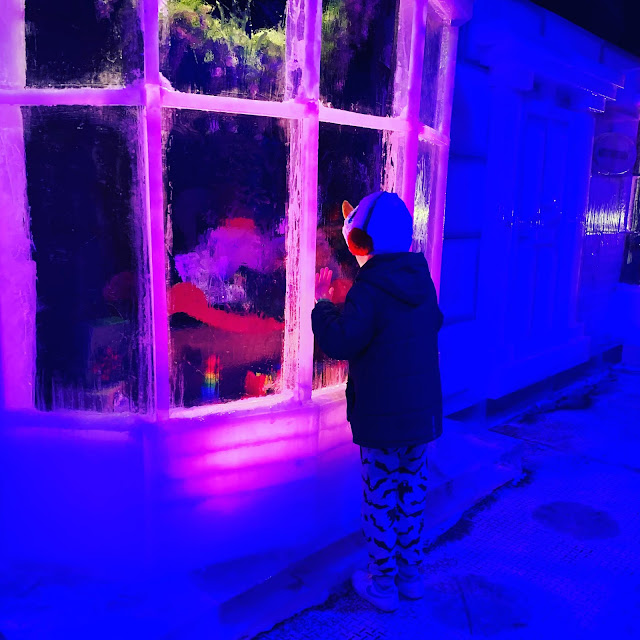 child peers into window of ice sculpture toy shop window  at Magical Ice Kingdom, Winter Wonderland, Hyde Park, 2019