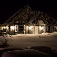 Une maison en hivers illuminée par un projecteur laser