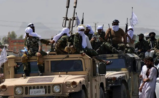 Taliban fighters sit on a US Army Humvee in Afghanistan. Photo: Arab News