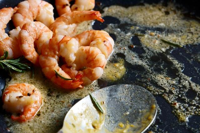 Plato con camarones en salsa de ostras con una cuchara de metal