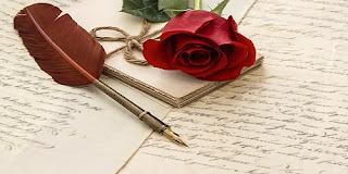 Rosa roja y un bolígrafo-pluma terminado en pluma de ave sobre una carta de amor.