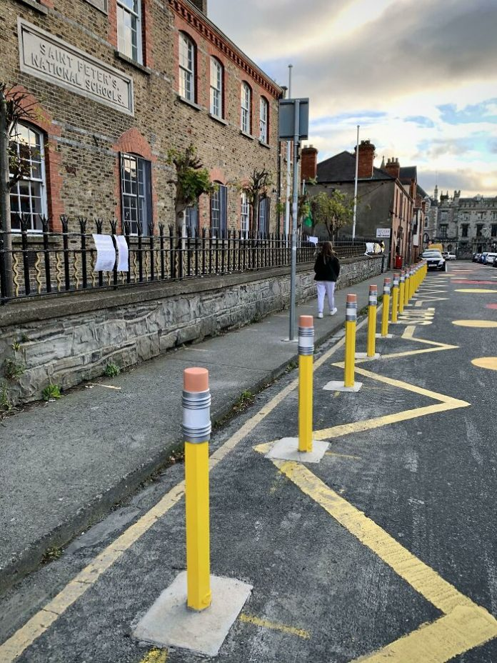 Not just boring road obstacles, but giant pencils separating the school grounds from the roadway.