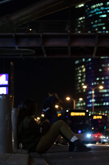 A female soldier is sitting waiting for her bus to arrive, next to the Azrieli center, with the Azrieli bridge and Afrisquare building in the background.