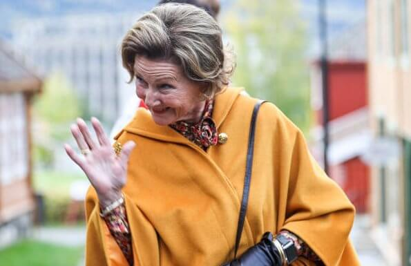King Harald of Norway was hospitalized. Queen Sonja wore a pussy-bow floral-print stretch-crepe blouse, and yellow vest, and brown trousers