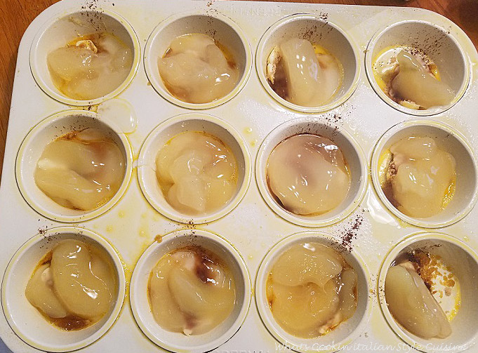 this is a muffin tin with apples and butter on the bottom then a layer of homemade cake batter on top getting ready to be baked in the oven