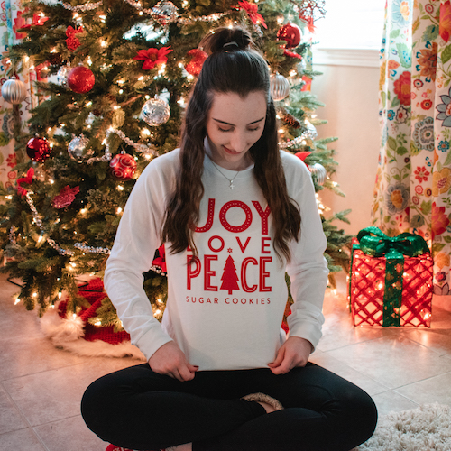 Madalyn sitting on floor in front of Christmas tree wearing the Candace Cameron Bure Joy Love Peace Long Sleeve T-Shirt.