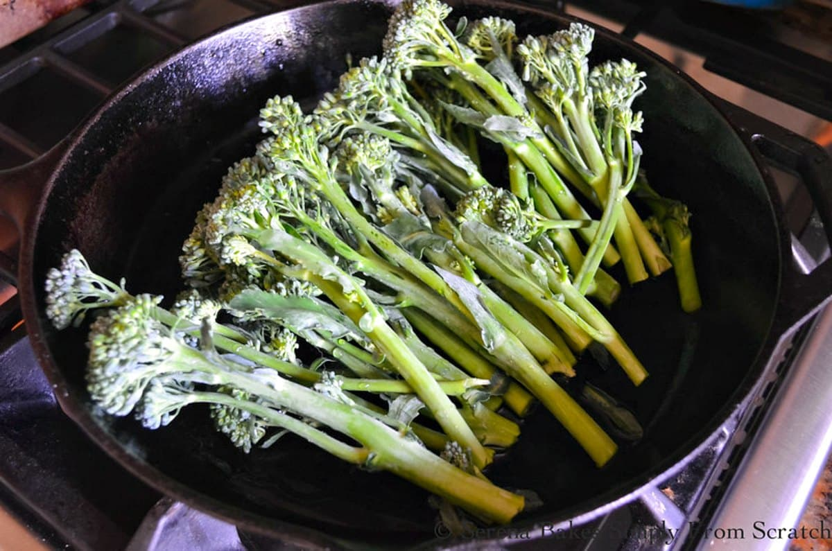 Cast Iron Skillet filled with washed Raw Broccolini.