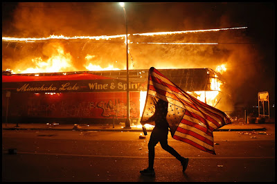 Man silhoutetted behind upside down US flag, walking in front of buildings on fire