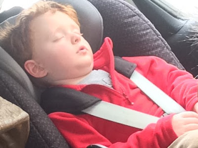 Little boy asleep in his car seat