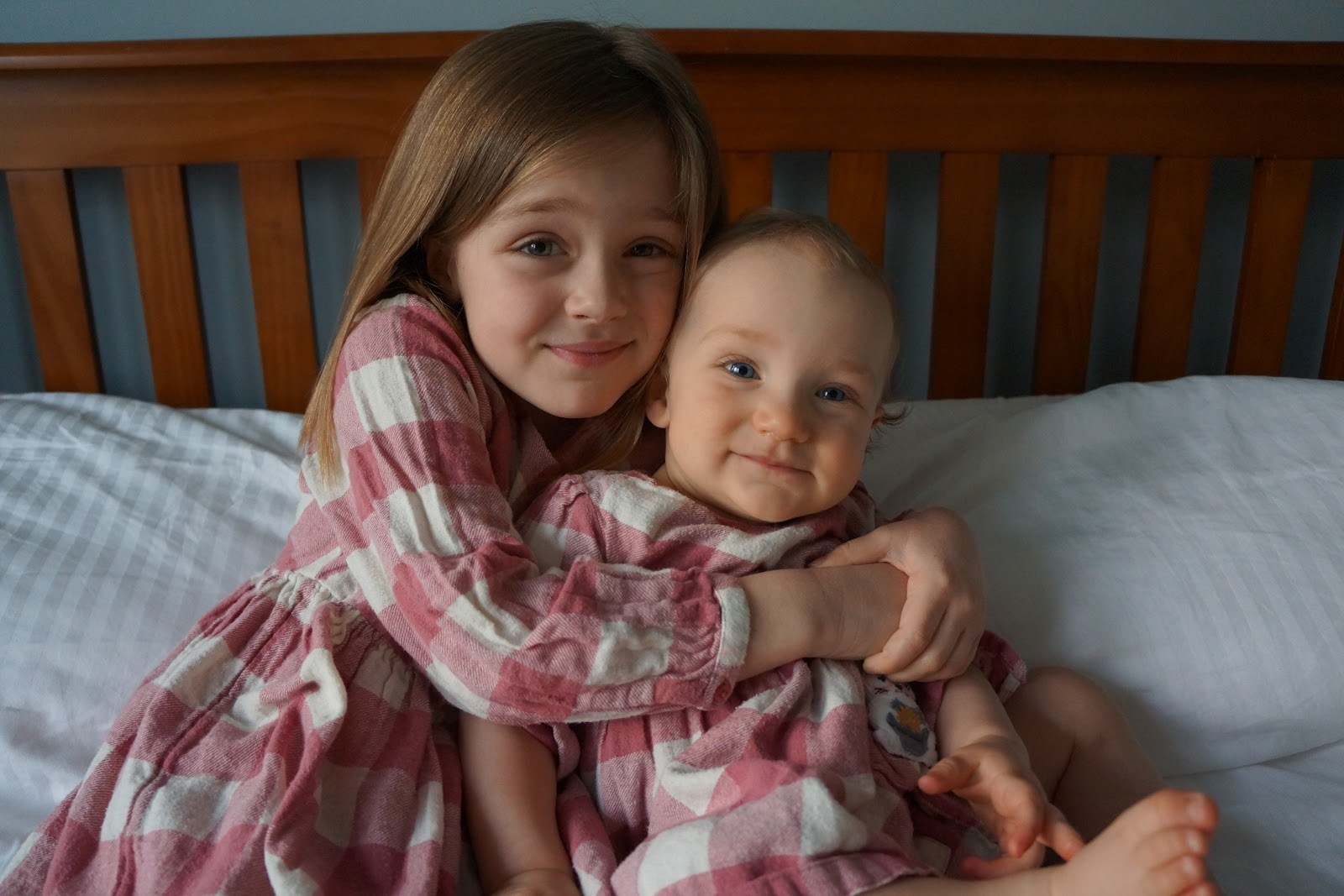 baby and sister in matching dresses cuddling