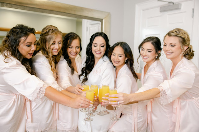 bride and bridesmaids toasting with mimosas